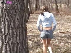 Tanned beauty Andi Pink is walking sexy in the woods in denim jeans