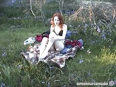Redhead teenager masturbates her snatch on the grass